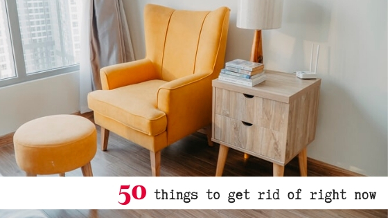 "yellow armchair and matching footstool alongside bedside table and lamp in a room with text overlay that reads ""50 things to get rid of right now"""